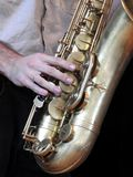 Close-up of a saxophonist playing his instrument, a saxophone. royalty free stock photography