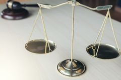 Close up of scales of justice and gavel on wooden table in a cou Stock Images