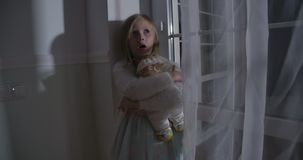 Close-up of scared Caucasian blond girl hugging doll and yelling. Portrait of frightened child standing next to the big