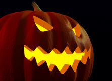 Close-up of a scary Halloween jack-o-lantern face glowing in the dark Stock Photo