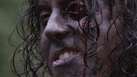 Close up of a scary smiling zombie with damaged eye