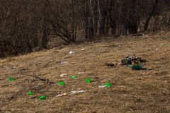 Close-up scattered garbage and lots plastic cups on spring grass left by tourists in mountains in forest stock images