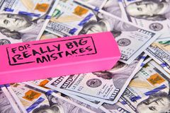 Close up scattered US Dollars with message on pink eraser for really big mistake. Fixing financial, business, taxes problems
