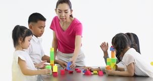 Asian teacher lets Asian students playing colorful wooden blocks toy together, concept for classroom. stock footage
