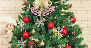 Close up scene video of beautiful Christmas tree. Close up scene video of beautiful Christmas tree, then someone`s hands decorated it by golden glitter balls stock footage