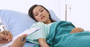 Close up scene video of doctor asking Asian female patient about her illness in hospital. stock footage