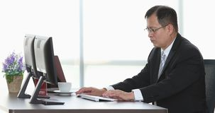 Senior businessman using computer in office. Close up scene video of senior Asian businessman using computer alone there are two monitors in modern office stock footage