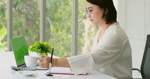 Asian businesswoman using laptop in office. stock footage