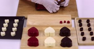 Someone removed the chocolate from mold. Close up scene video of someone removed chocolates from the heart shaped mold, arrange the chocolate on a wooden stock video footage