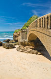 Close up of scenic stone footbridge on sandy beach in scenic seascape of atlantic coast in blue sky in vertical position, biarritz Stock Images