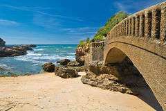 Close up of scenic stone footbridge on sandy beach in scenic seascape of atlantic ocean with waves in blue sky, biarritz, basque c Stock Images