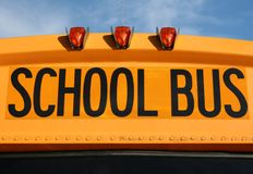 Close up of a school Bus. Close-up view of a yellow school bus sign and lights with blue sky background royalty free stock image