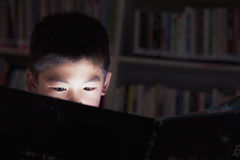 Close up of a schoolboy reading a book with his face lit up Royalty Free Stock Images