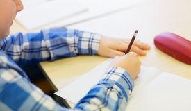 Close up of schoolboy writing test at school Royalty Free Stock Image