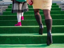 Close-up of a schoolgirl`s leg and her mom are walking up the stairs to school royalty free stock photos