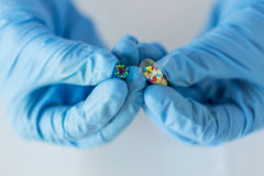 Close up of scientist hands holding pill in lab Stock Image