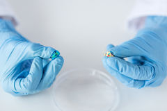 Close up of scientist hands holding pill in lab Stock Images