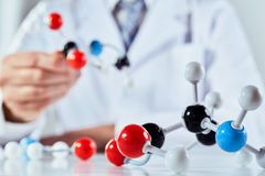 Scientist with coloured molecular structure models. A close up of a scientist in a lab coat demonstrating with molecular structure models royalty free stock images