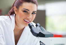 Close up of a scientist posing with a microscope Stock Image
