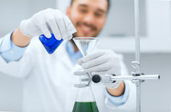 Close up of scientist with test tubes and funnel. Science, chemistry, biology, medicine and people concept - close up of scientist filling test tubes with funnel Royalty Free Stock Photo