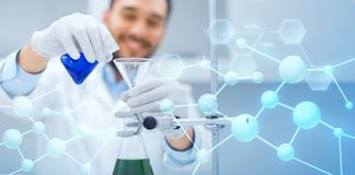 Close up of scientist with test tubes and funnel. Science, chemistry, biology, medicine and people concept - close up of scientist filling test tubes with funnel royalty free stock photography