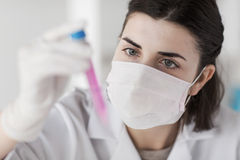 Close up of scientist with tube making test in lab Royalty Free Stock Images
