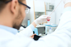 Close up of scientist with tube and pipette in lab. Science, chemistry, biology, medicine and people concept - close up of male scientist with test tube and Royalty Free Stock Photo