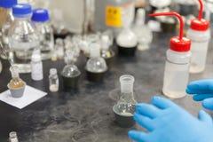 Scientist working in laboratory mixing liquids. Close up of Scientist working in laboratory mixing liquids Royalty Free Stock Image