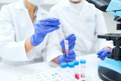 Close up of scientists filling test tube in lab Royalty Free Stock Image