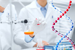 Close up of scientists filling test tube in lab Stock Image