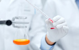 Close up of scientists filling test tube in lab Royalty Free Stock Photos