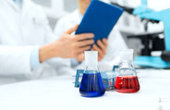 Close up of scientists with flasks and tablet pc. Science, chemistry, technology, biology and people concept - close up of scientists with glass tes flasks and Stock Images
