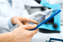 Close up of scientists hands with tablet pc in lab Royalty Free Stock Photo
