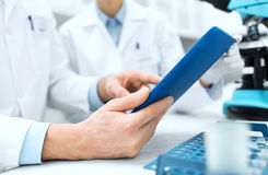 Close up of scientists hands with tablet pc in lab Stock Image