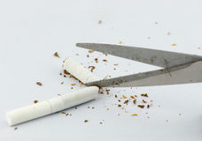 Close-up Of scissor cutting The Cigarette Stock Photo