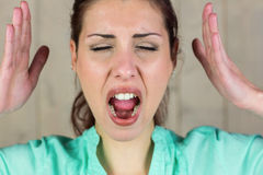 Close-up of screaming woman gesturing with eyes closed Stock Image