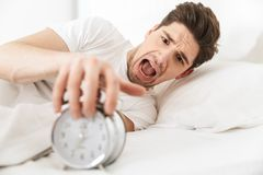 Close up of a screaming young man. Turning alarm off in the morning while lying in bed Royalty Free Stock Photos