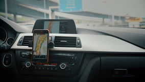 Close up on screen navigation tracking vehicle location and route while driving on road. GPS navigation on smartphone