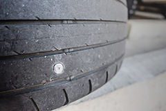 Close up of screw nail puncturing car tire Royalty Free Stock Image