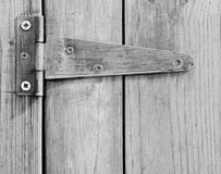 Close up of screwed hinge on wooden door. Royalty Free Stock Photos