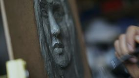 Close-up of Sculptor creating sculpture of human`s face on canvas in art studio. Indoors stock footage