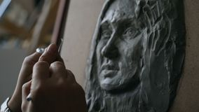 Close-up of Sculptor creating sculpture of woman`s face on canvas in art studio. Indoors stock video footage