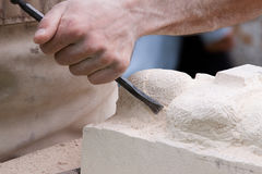 Close up of a sculptor at work. At work on a sandstone block Royalty Free Stock Photography