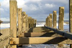 Close up of sea defence`s. Sea defence`s known as groyne`s which are sturdy wooden built structures to stop beach erosion on the north Norfolk coast between Royalty Free Stock Photos