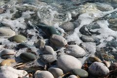 Close-up of sea pebbles in the bubbling water stock images