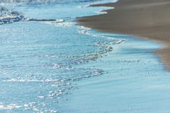 Close up of the sea water affecting the sand on the beach, sea w Royalty Free Stock Photos