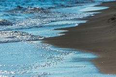 Close up of the sea water affecting the sand on the beach, sea w Royalty Free Stock Images