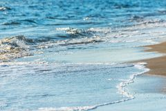 Close up of the sea water affecting the sand on the beach, sea w Stock Images