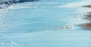 Close up of the sea water affecting the sand on the beach, sea w Royalty Free Stock Photo