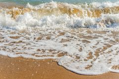 Close up of the sea water affecting the sand on the beach, sea w Stock Photos